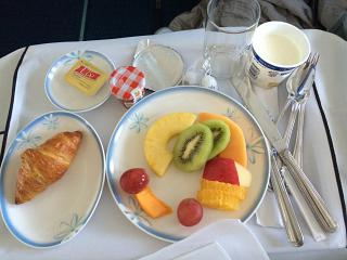 A croissant and fruit are part of Breakfast in the business class flight on Air Tahiti Nui on a flight Tokyo-Papeete