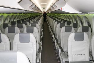 Вид спереди на пассажирский салон в самолете Airbus A220-300 авиакомпании airBaltic