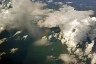 Rainbow between the clouds in flight over Thailand