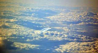 The plane flies above the clouds over France