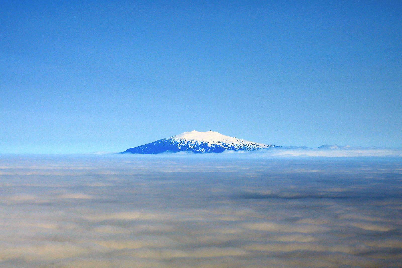 Вулкан выше облаков в небе над Исландией