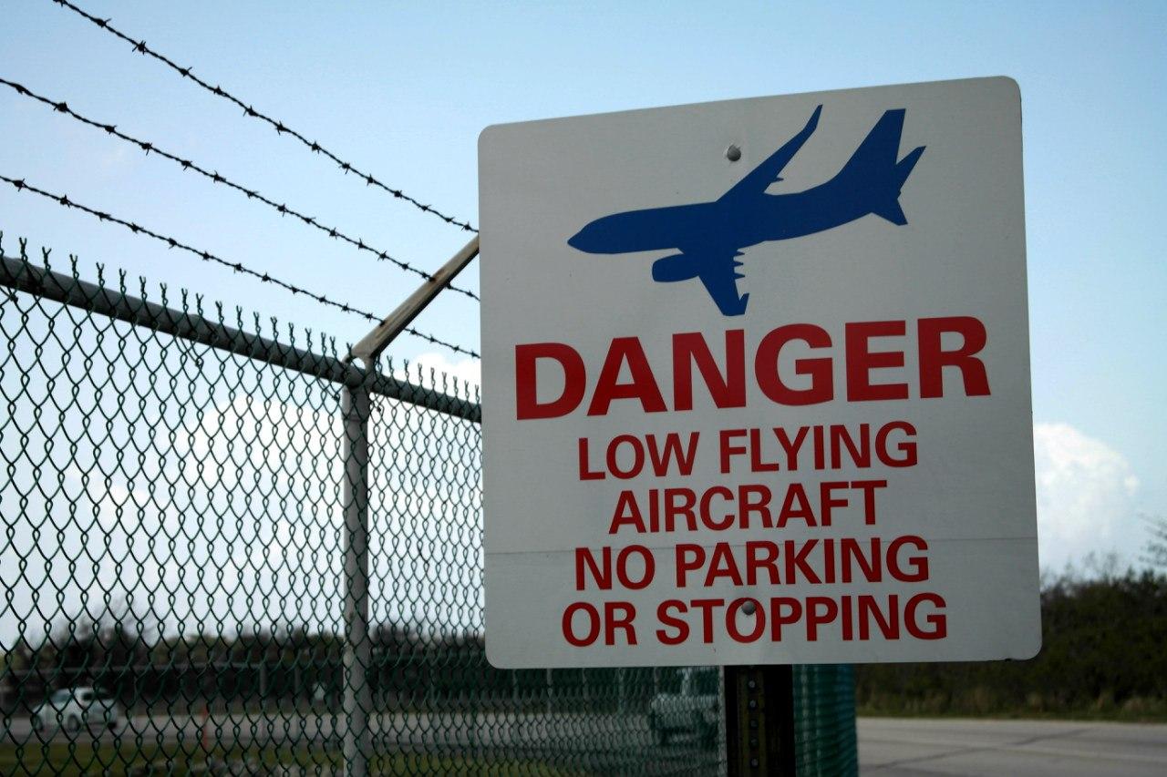 Табличка о низколетящих самолетах в аэропорту Джорджтаун на Каймановых островах