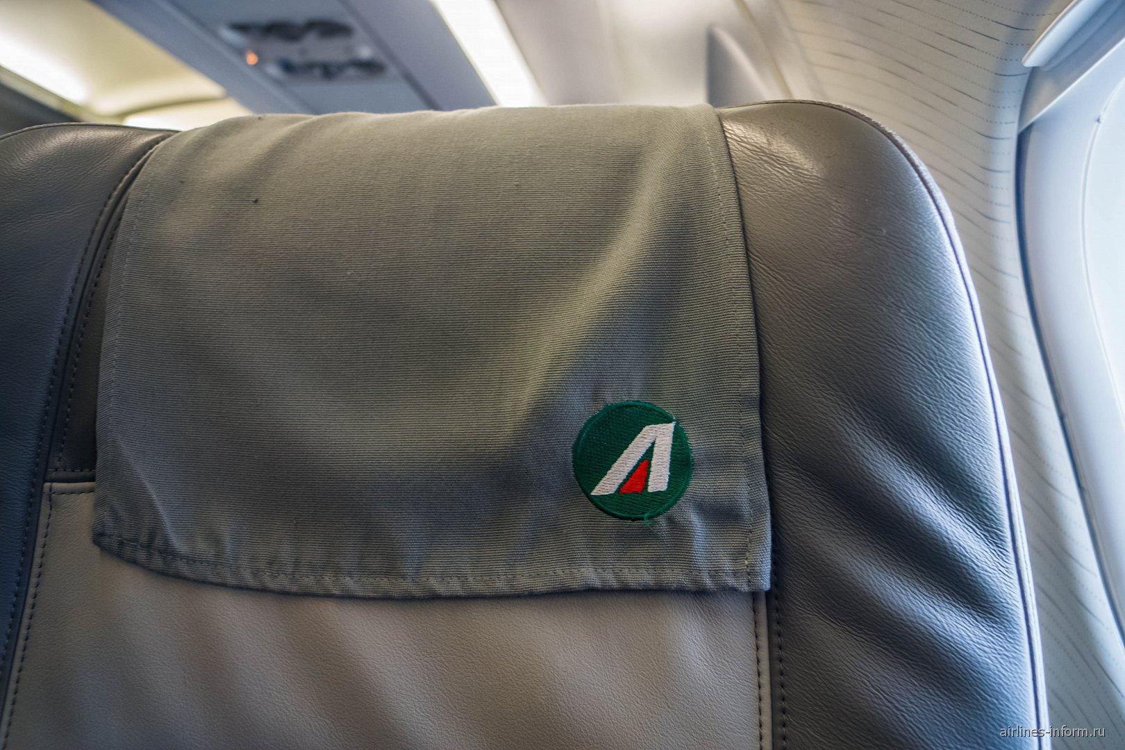 "Вышитый логотип ""Alitalia"" на подголовнике кресла"