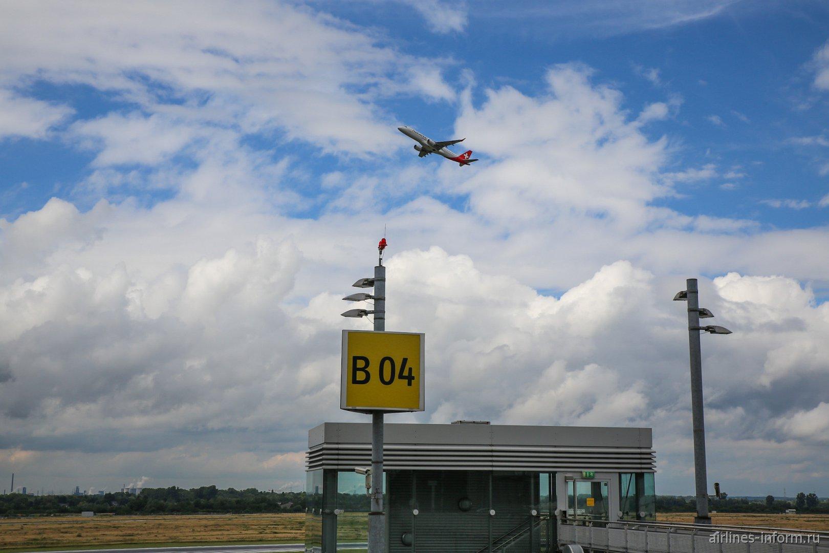 Вид на взлетающий самолет со смотровой площадки в аэропорту Дюссельдорфа
