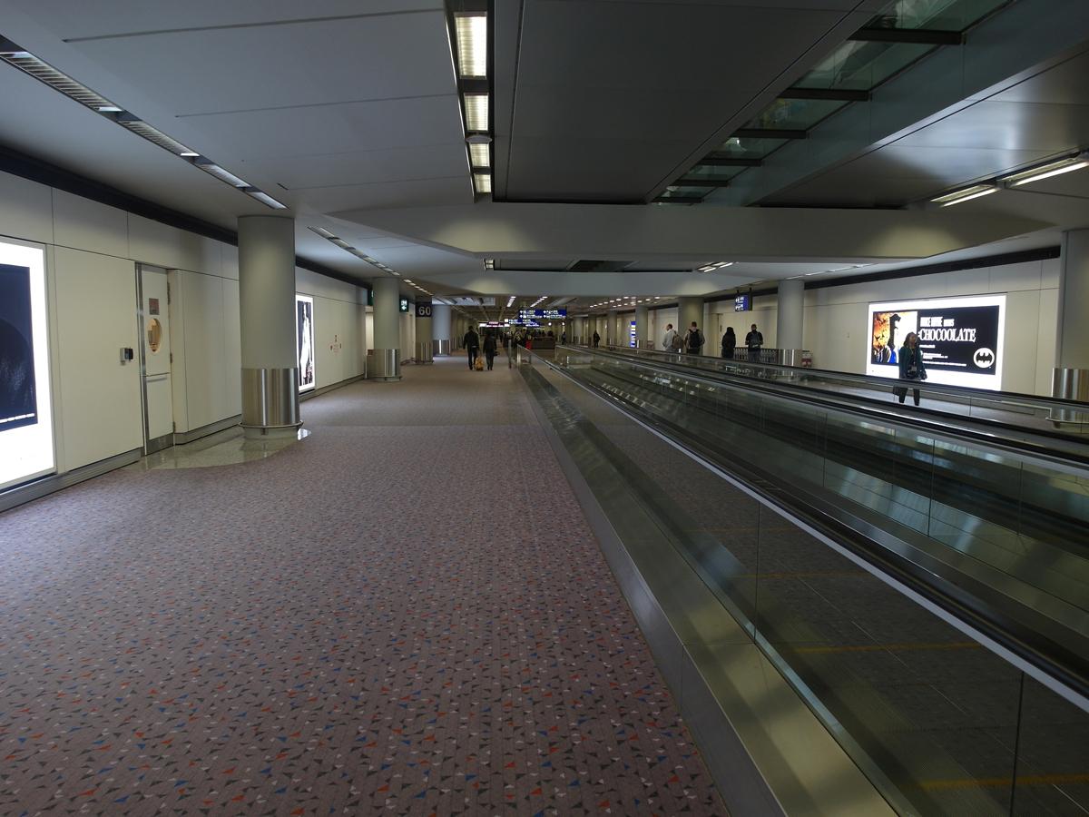 Длинные коридоры к гейтам в аэропорту Гонконга