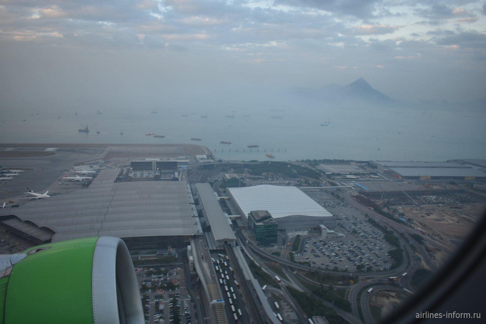 Вид на пассажирские терминалы аэропорта Гонконг при взлете
