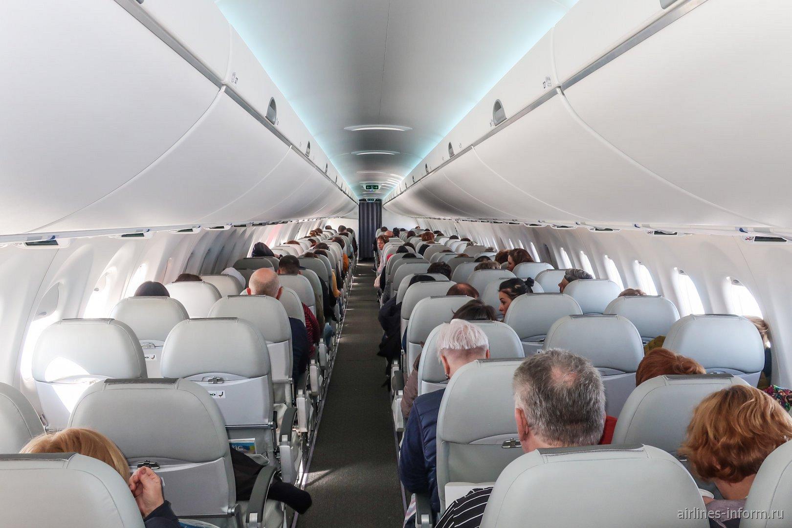 Вид сзади на пассажирский салон в самолете Airbus A220-300 авиакомпании airBaltic